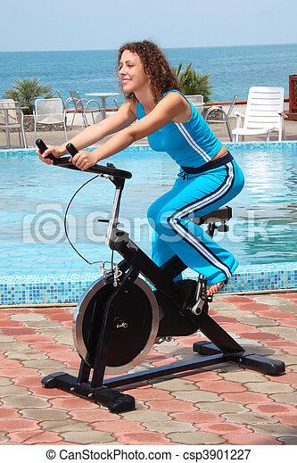 Chica sonriente en un aparato de entrenamiento en bicicleta al aire libre - csp3901227