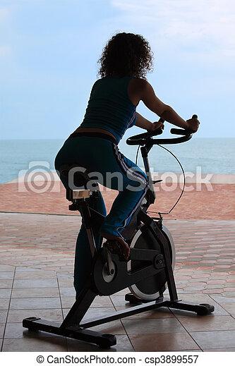 Silueta de chica en un aparato de entrenamiento en bicicleta al aire libre - csp3899557