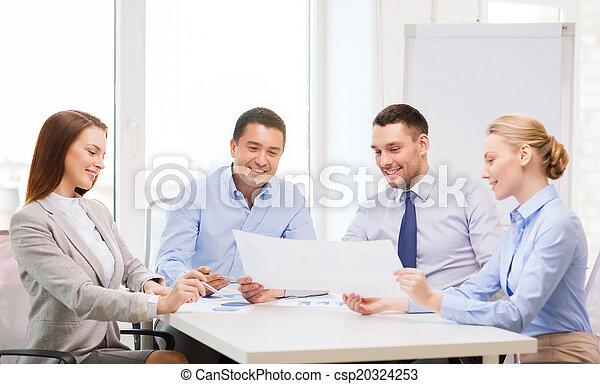 Equipo de negocios sonriente teniendo una discusión en la oficina - csp20324253