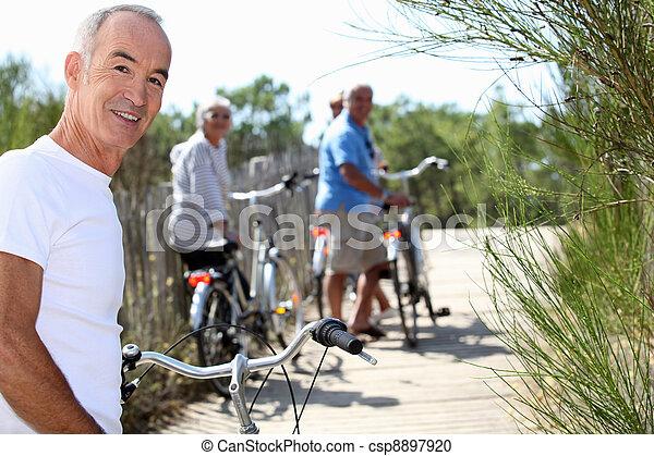 Hombres mayores y mujeres en bicicleta - csp8897920
