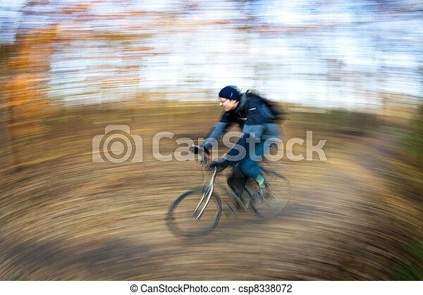 Cabalgando en bicicleta en un parque en un hermoso día de otoño y otoño - csp8338072