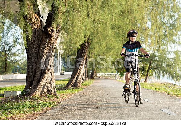 Mujer asiática mayor montando en bicicleta - csp56232120