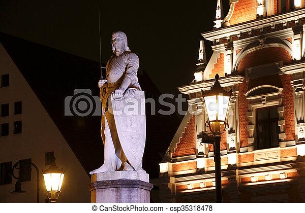 Escultura de roland en la plaza del ayuntamiento por la noche, riga, latvia - csp35318478