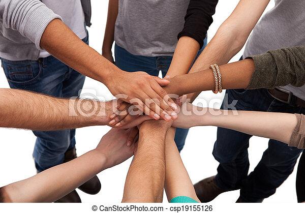 Estudiantes universitarios apilando manos - csp19155126