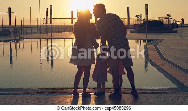 Familia feliz con tres niños admirando el atardecer reflejado en la superficie de la piscina - csp45083296