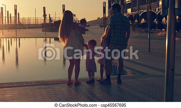 Familia feliz con tres niños admirando el atardecer reflejado en la superficie de la piscina - csp45567695
