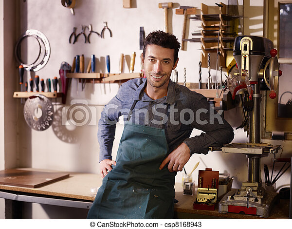 Feliz artesano italiano en el trabajo, sonriendo en el taller de guitarras - csp8168943