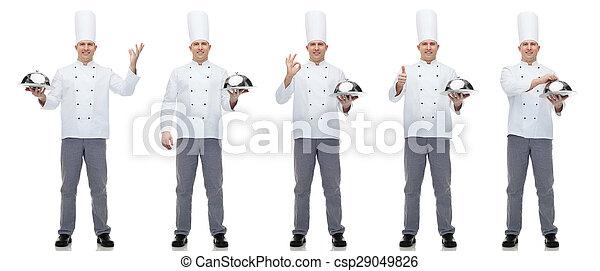 Feliz cocinero masculino sosteniendo cloche - csp29049826