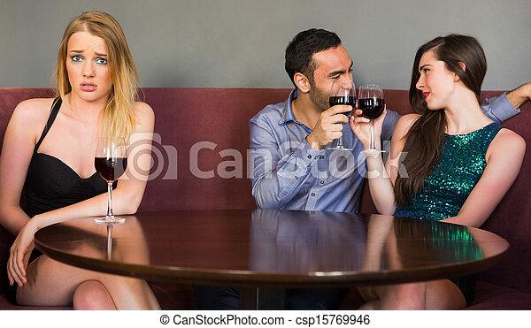 Una mujer rubia celosa como dos personas coquetean con ella en un club mirando la cámara - csp15769946