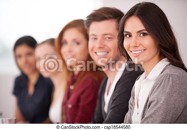 Gente en el seminario. Una joven atractiva sonriendo a la cámara mientras otras personas se sientan detrás de ella en una fila - csp18544580