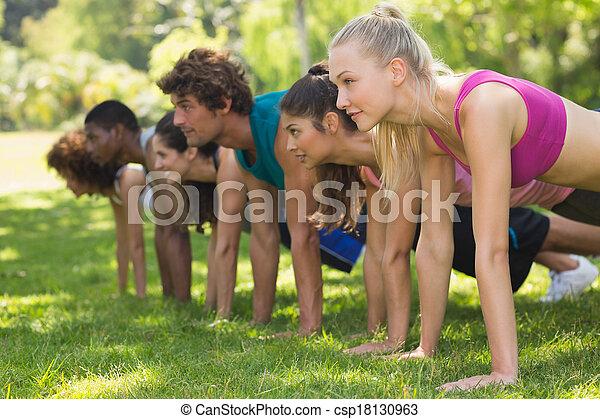 Grupo de personas en forma haciendo flexiones en el parque - csp18130963