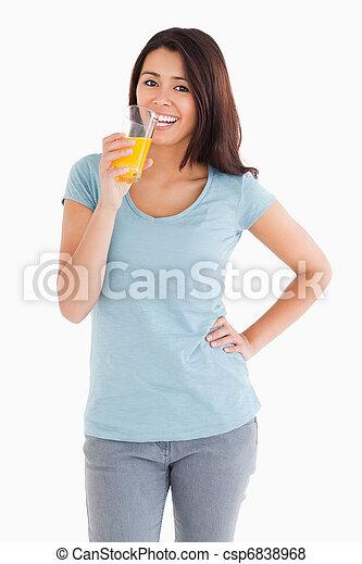 Hermosa mujer bebiendo un vaso de jugo de naranja - csp6838968