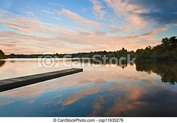 Hermoso atardecer sobre el lago de otoño con reflejos cristalinos - csp11635276