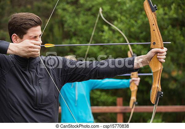 Un hombre guapo que practica tiro al arco - csp15770838