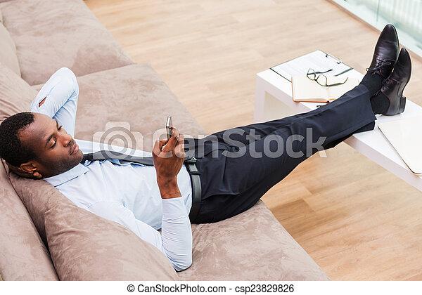 Relajarse después del trabajo hecho. La mejor vista del apuesto joven africano en ropa formal acostado en el sofá con las piernas en un escritorio y sosteniendo el teléfono móvil - csp23829826