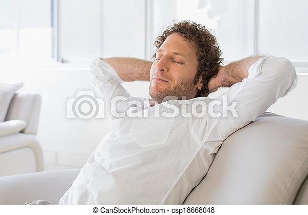 Hombre relajado sentado con las manos detrás de la cabeza en casa - csp18668048