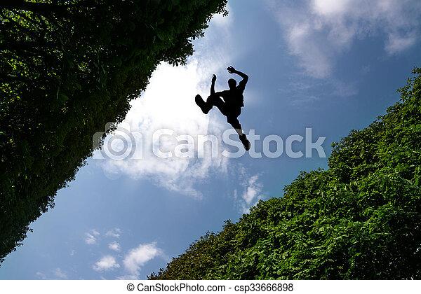 Hombre saltando sobre arbustos - csp33666898