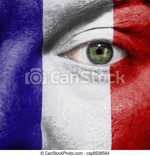 La bandera pintada en la cara con el ojo verde para mostrar apoyo a Francia - csp9508564