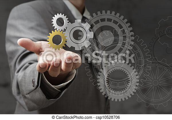 La mano muestra ruedas de engranaje - csp10528706