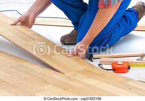 Hombre poniendo suelo laminado - csp21852196