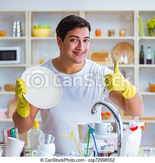 Hombre mostrando pulgares arriba lavando platos - csp72998552