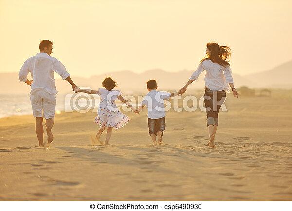 Los jóvenes felices se divierten en la playa al atardecer - csp6490930