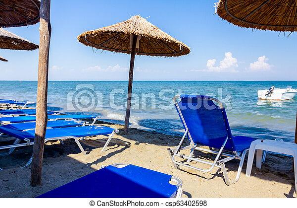Los paraguas con percheros, se colocan al lado de la costa, a lo largo del borde del agua - csp63402598