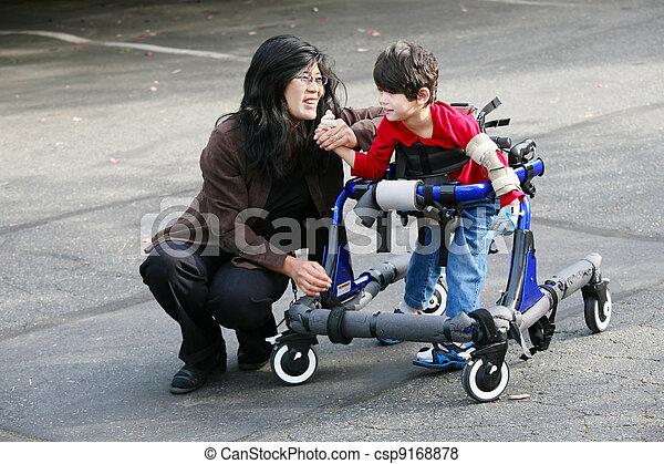 Madre con un hijo discapacitado caminando al aire libre con andador, equipo de movilidad médica - csp9168878