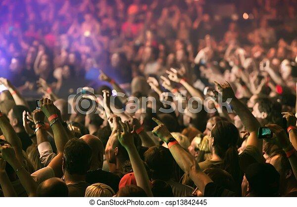 Gente aplaudiendo y levantando las manos en un concierto de música en vivo - csp13842445