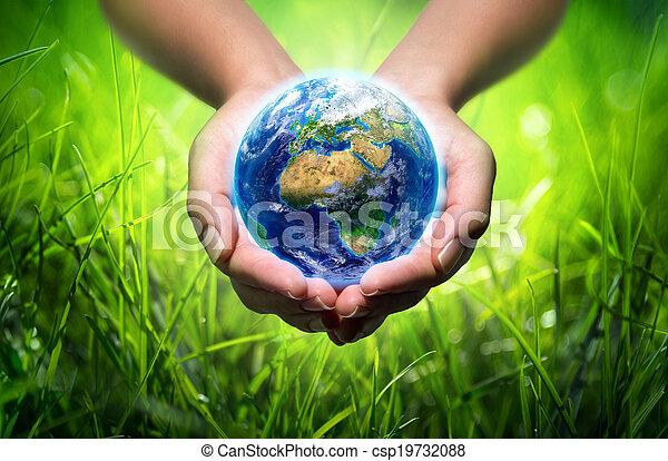 Tierra en manos, fondo de hierba - csp19732088