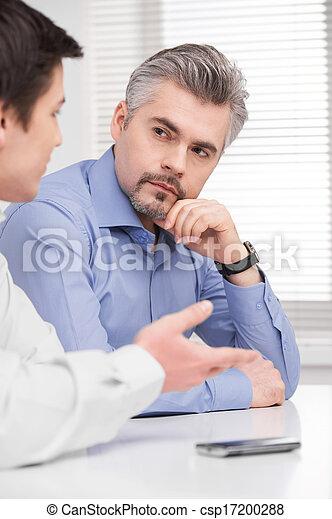 Retrato de un serio hombre de negocios de mediana edad. Sentados y escuchando a un joven colega adulto - csp17200288