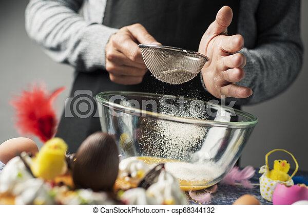 Preparando una Mona de Pascua, un pastel de Pascua español - csp68344132