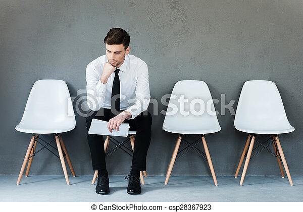 Mucho tiempo esperando. Pensivo joven hombre de negocios sosteniendo papel y sosteniendo la mano en la barbilla mientras sentado en la silla contra el fondo gris - csp28367923