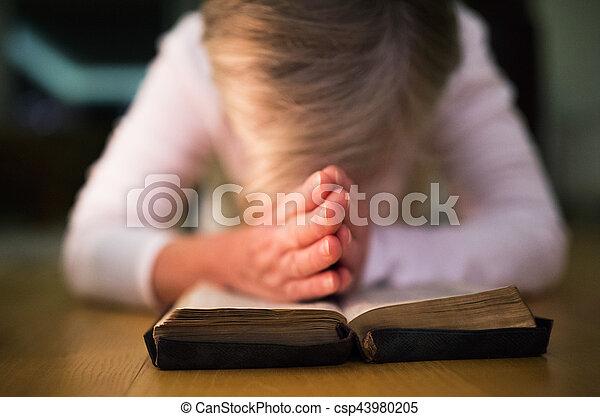 Una mujer irreconocible rezando, con las manos juntas en su Bibl - csp43980205