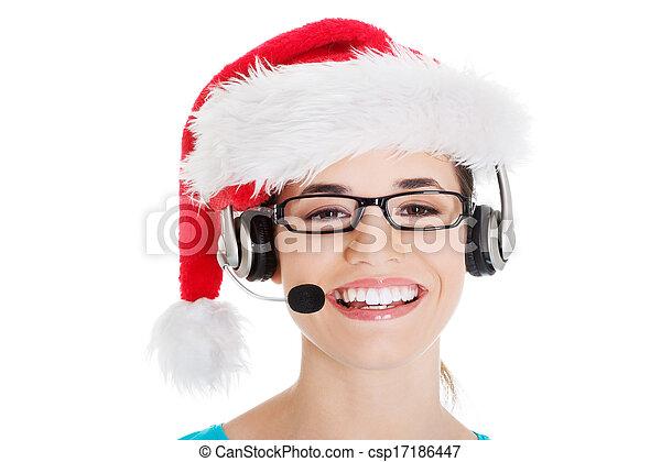 Una joven mujer casual con sombrero de Santa y micrófono y auriculares. - csp17186447