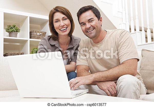 Una pareja de hombres felices con computadora portátil en casa - csp6013577