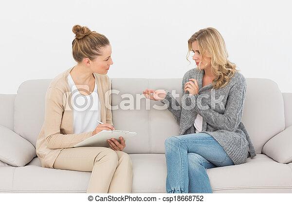 Mujer rubia hablando con su terapeuta en el sofá - csp18668752