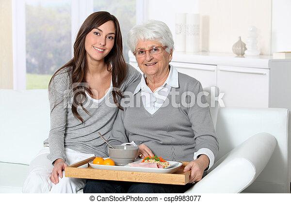 Mujer mayor y cuidadora sentada en el sofá con bandeja de almuerzo - csp9983077