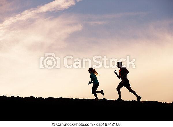 Silueta de hombre y mujer corriendo juntos hacia la puesta del sol, concepto de en forma de bienestar - csp16742108