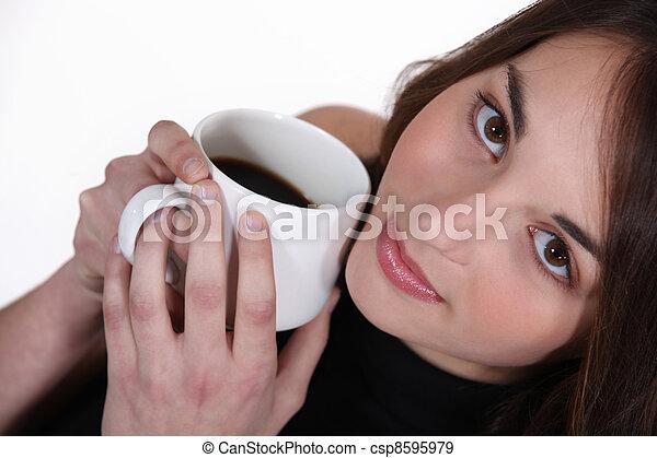 Mujer sosteniendo taza de café a la cara - csp8595979