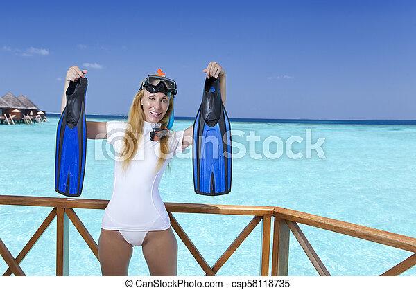 Una joven mujer bonita en equipo para un snorkeling en la terraza sobre el mar. Maldivas - csp58118735