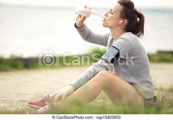 Mujer trotamundos descansando y bebiendo agua embotellada - csp15403653