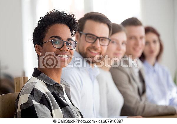 Feliz equipo multiracial sonriendo mirando a la cámara - csp67916397