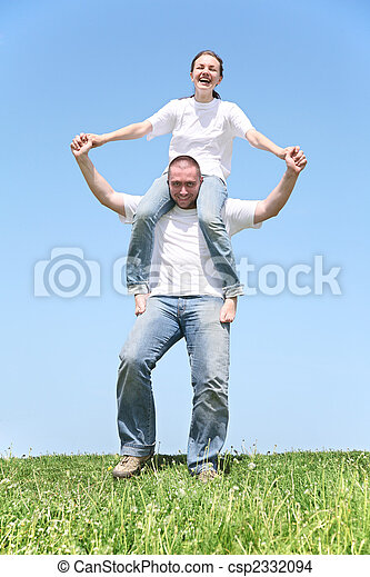 Chica sobre hombros de chico sobre hierba - csp2332094