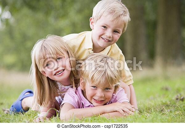 Tres niños jugando al aire libre sonriendo - csp1722535