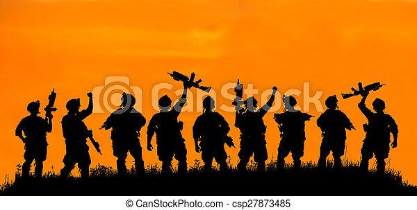 Silueta de soldado o oficial con armas al atardecer. - csp27873485