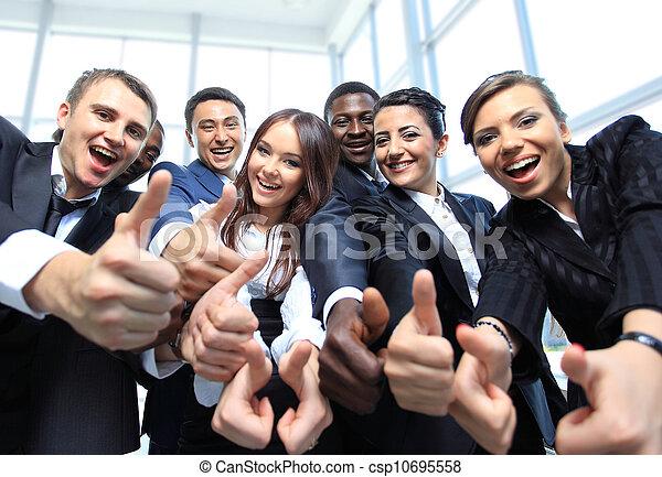 Feliz equipo de negocios multiétnico con pulgares arriba en la oficina - csp10695558