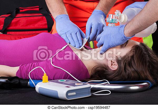 Paramédicos usando desfibrilador en un paciente - csp19594487