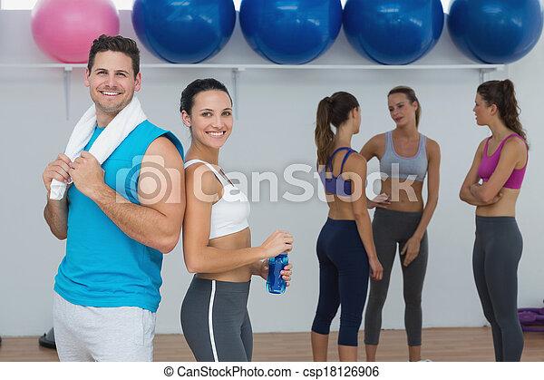 Pareja sonriente con clase de fitness en el fondo - csp18126906