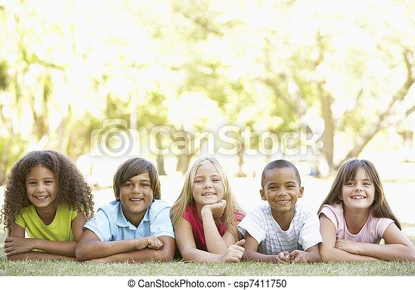 Un grupo de niños tirados en el estómago del parque - csp7411750